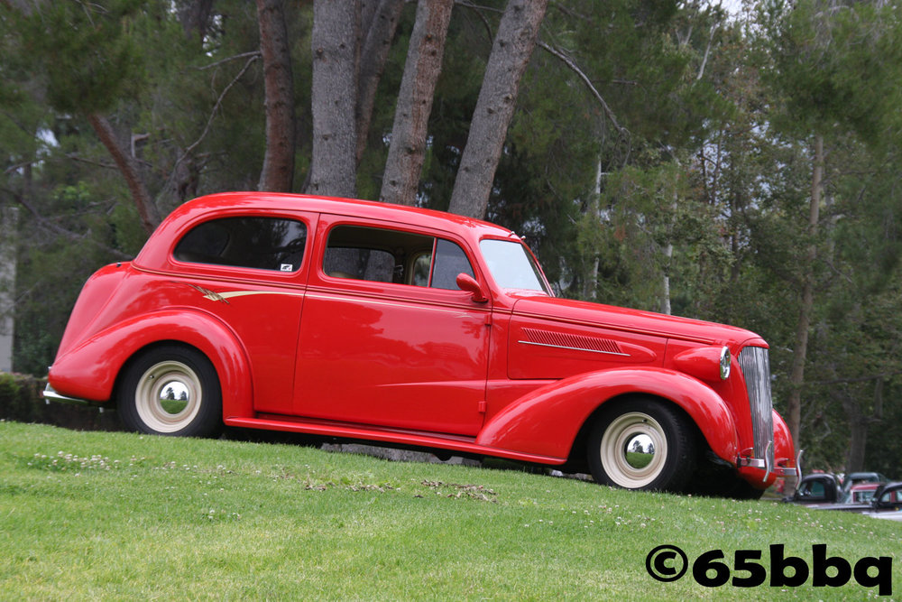 Red ride sitting on the lawn at Southern California Car Show 65bbq