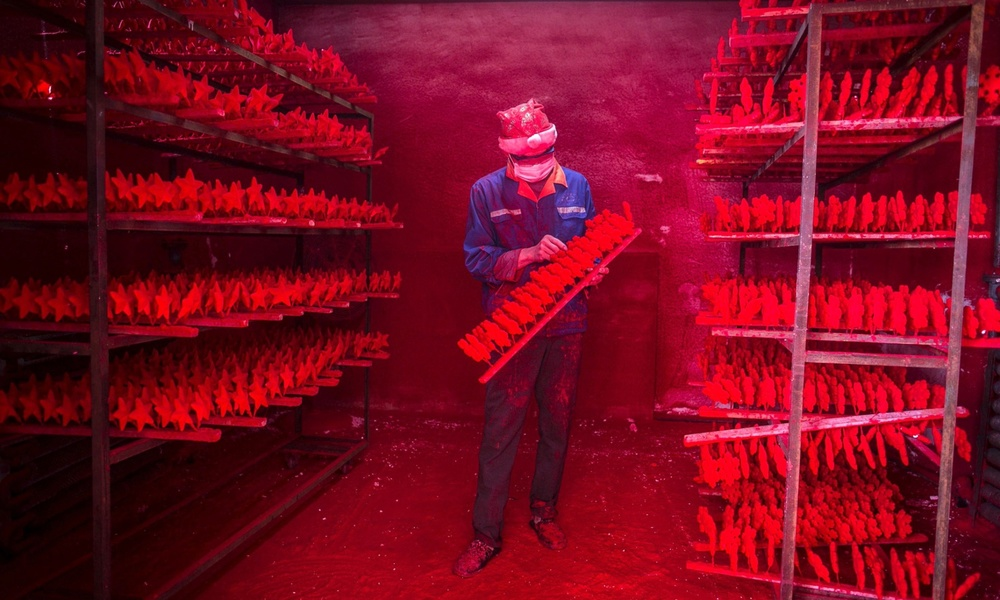 The two men produce 5,000 red snowflakes a day, and get paid around £300 a month.Photograph: China Daily/Reuters
