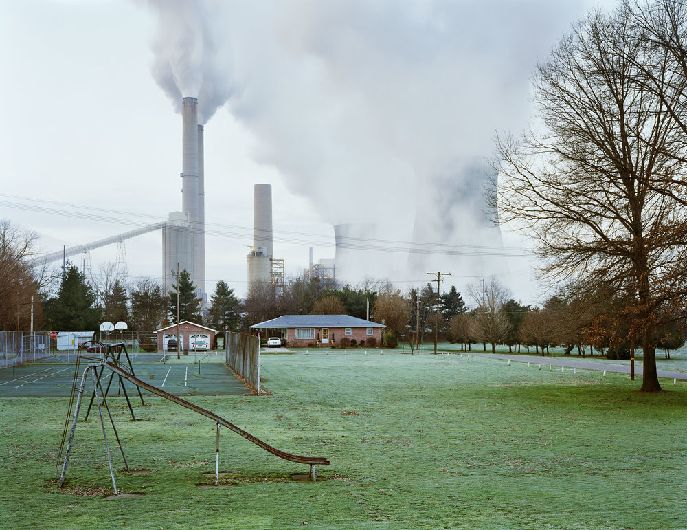 "Cheshire, Ohio II. 2004 © Mitch Epstein courtesy Aperture  ""  I went to Cheshire, Ohio, in 2003 to make pictures of a town that had been bought out by American Electric Power. The townspeople had been complaining of toxic contamination from the local coal-fired power plant, and had agreed, for a price, to keep silent and never sue AEP. It was when I returned home to New York, and couldn't get Cheshire and its residents out of my mind, that I began the series 'American Power,' in an effort to understand how energy functions: who makes it; who and what gets hurt by it; who profits from it; and what might be its, and therefore the nation's, future ."" - Mitch Epstein"