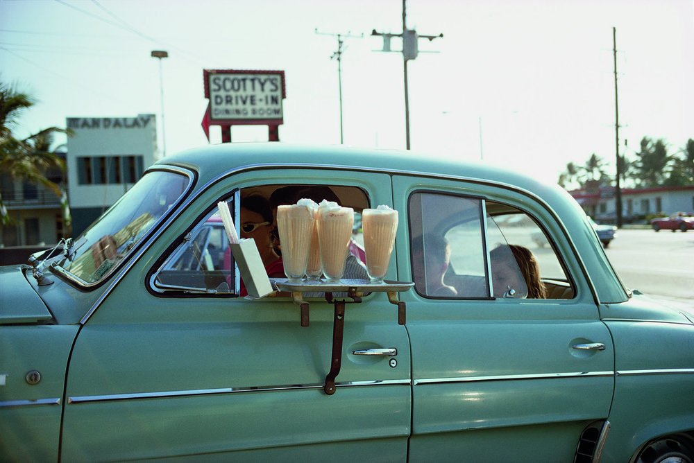 "Scotty's Drive in. Florida. 1967 © Joel Meyerowitz courtesy Aperture   "" Here's Scotty's   Sometimes when you're traveling in the car all day, on the lookout for life on the fly, a great thirst comes over you and that desire for the next event evaporates immediately upon seeing an old-fashioned diner, I mean the real thing, not some dolled-up imitation serving prepackaged crap, but a place where some degree of reverence for the past lets you know that a milkshake from childhood can be found there. And here's Scotty's.   Mmmmmm"""