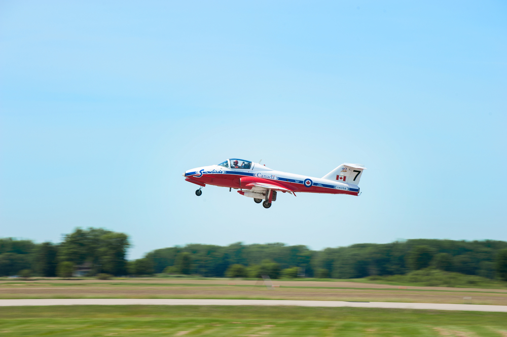 Panning the camera with a slow shutter speed as the snowbirds take off to the skies