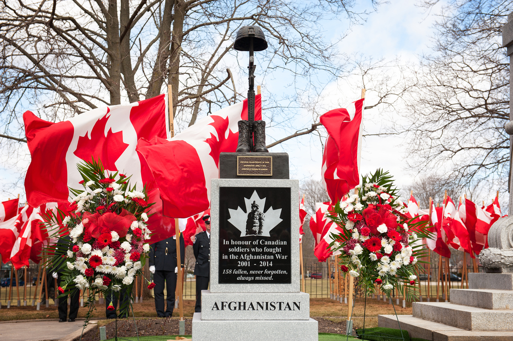 Afghanistan War Monument a.k.a THE BATTLE CROSS Sits Proud alongside the Woodstock ON. Cenotaph. 158 Canadian Flags dance in the wind, each with a fallen soldiers name on the wooden shaft.