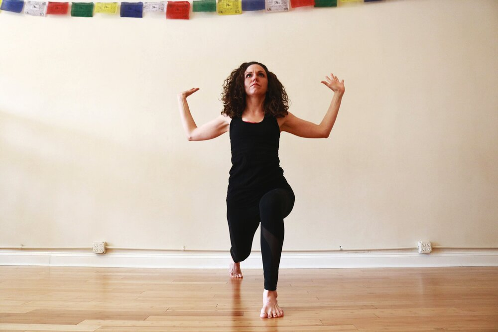 Teacher Angie Panozzo in a high lunge with an arm variation.