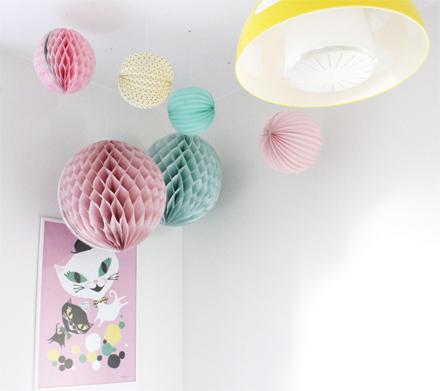 Pastelliga pappersbollar i olika storlekar hänger i taket, över sängen. Den gula lampan är från IKEAs barnavdelning.