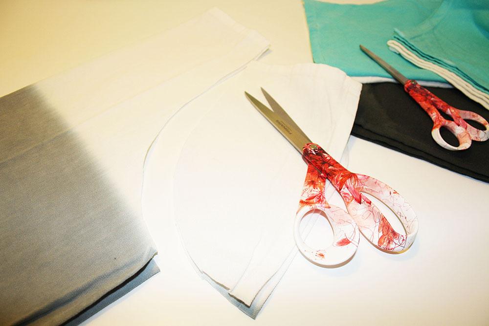 Börja med att lägga ena kökshanduken dubbelt och klipp bort hörnen i en rund form.