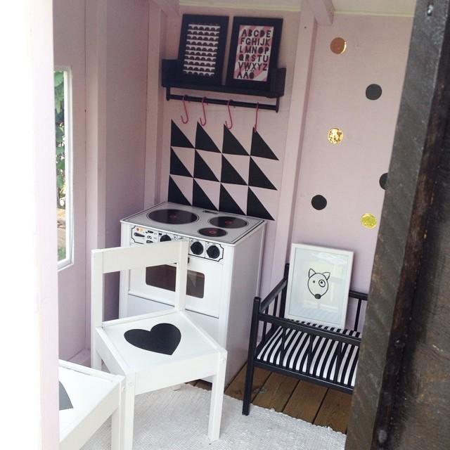 Jag tog en grön loppisfyndad docksäng och spraymålade svart, vägghyllan med stång är från IKEA och sprayades också svart. De vita stolarnas hjärtan, prickarna på väggenoch kaklet klippte jag till av dekorplast.