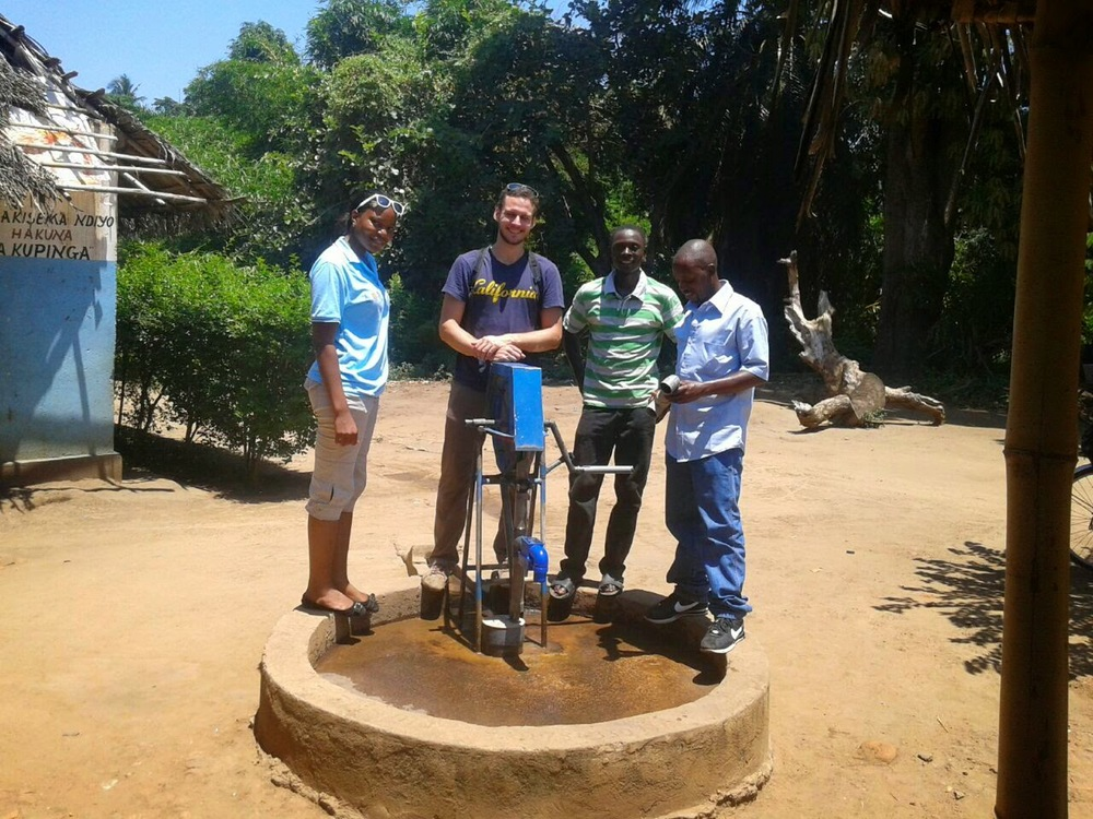 From left: Alphoncia, Pump for Life program manager, Austin from WellDone, Thomas, a MSBAI driller, and Riziki, Pump for Life's Idete-based mechanic, at a pump with MoMo installed.