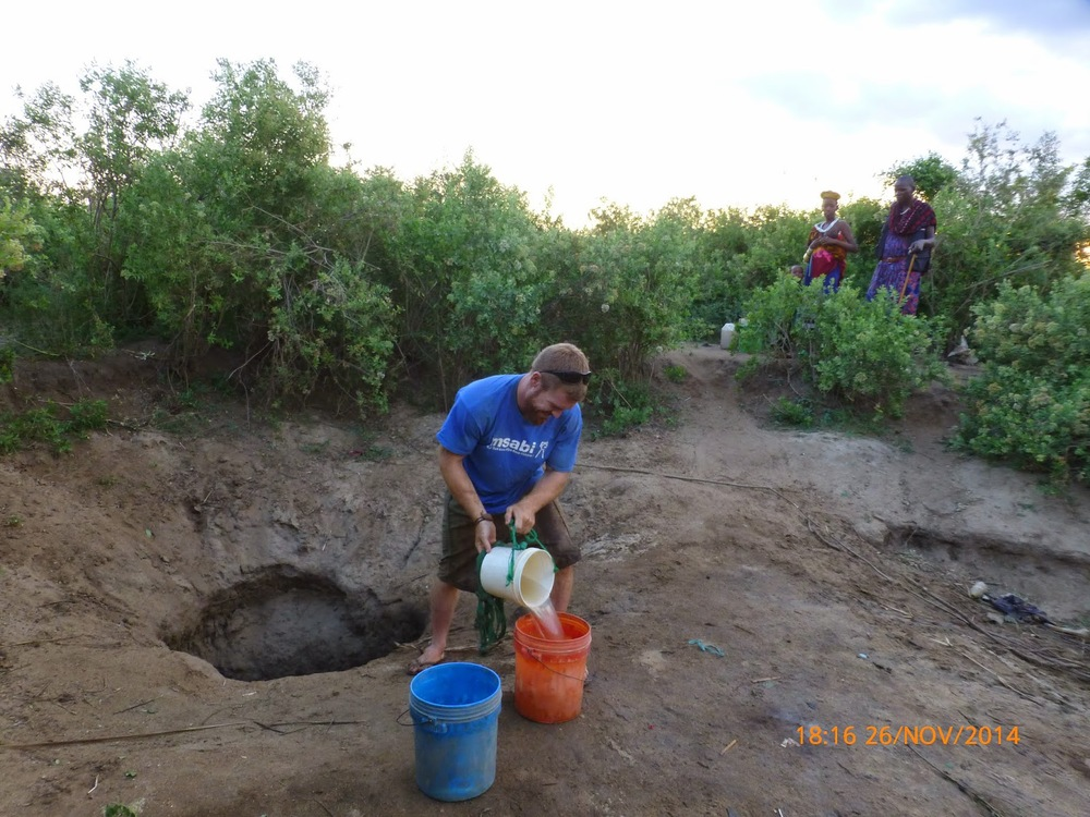 Photo 3 : Collecting washing water from the shallow open well, previously used as the principle water source within the community.