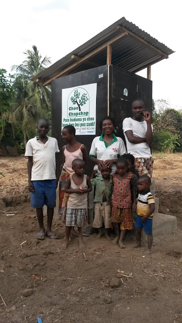 Users in a family photo in front of the their new toilet at Lumemo village