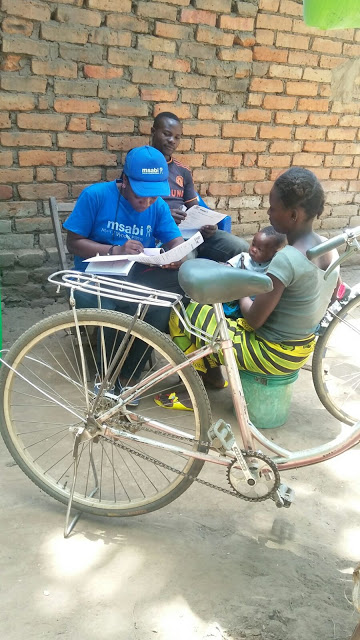 Miss Paskalina Kakweche registering new clients in the field after passing through the contact with the client.