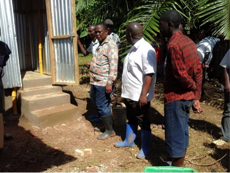 Kilombero District Commissioner, Leffi Gembe (in black rain boots), and other Government officials examining the toilet built by MSABI