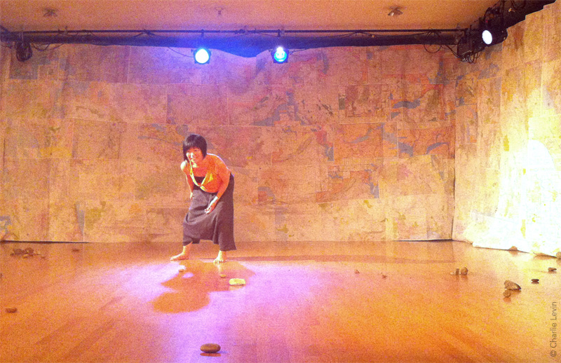 Performer Tomoko Hiraoka performing in Homing Devices. Set is constructed out of AAA maps sewn together to create full-scale fabric.