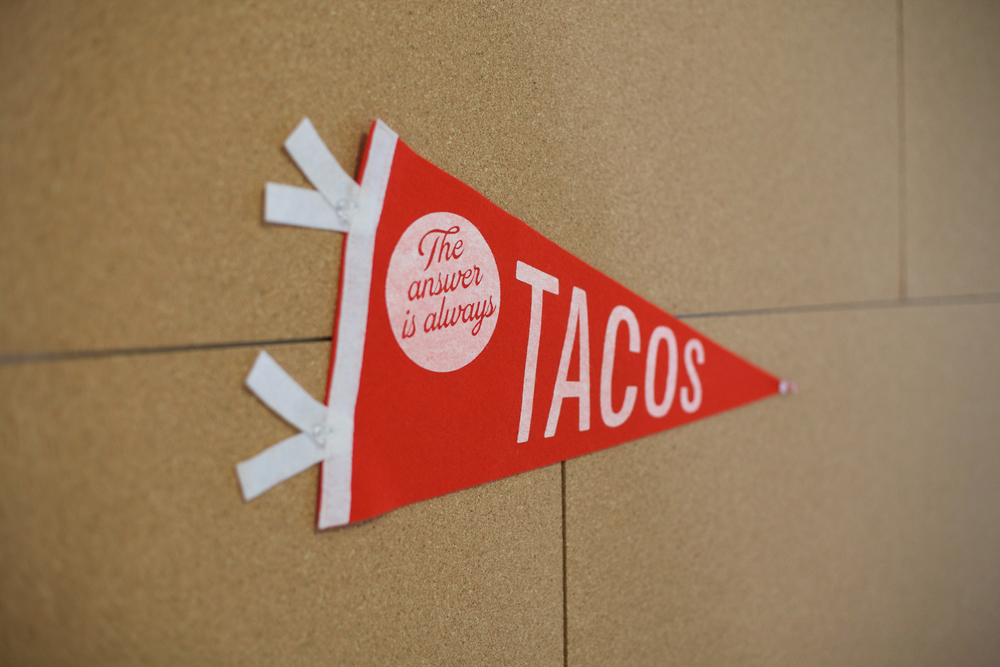 zmaic-one-month-interior-design-conference-room-corkboard-wall-the-answer-is-always-tacos-pennant.jpg