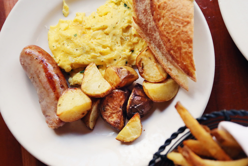 Two scrambled eggs with herbs, with potatoes, chicken & pork sausage, and baguette