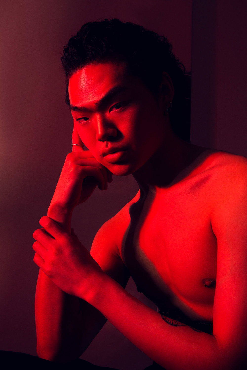 Red light closeup of asian male model.