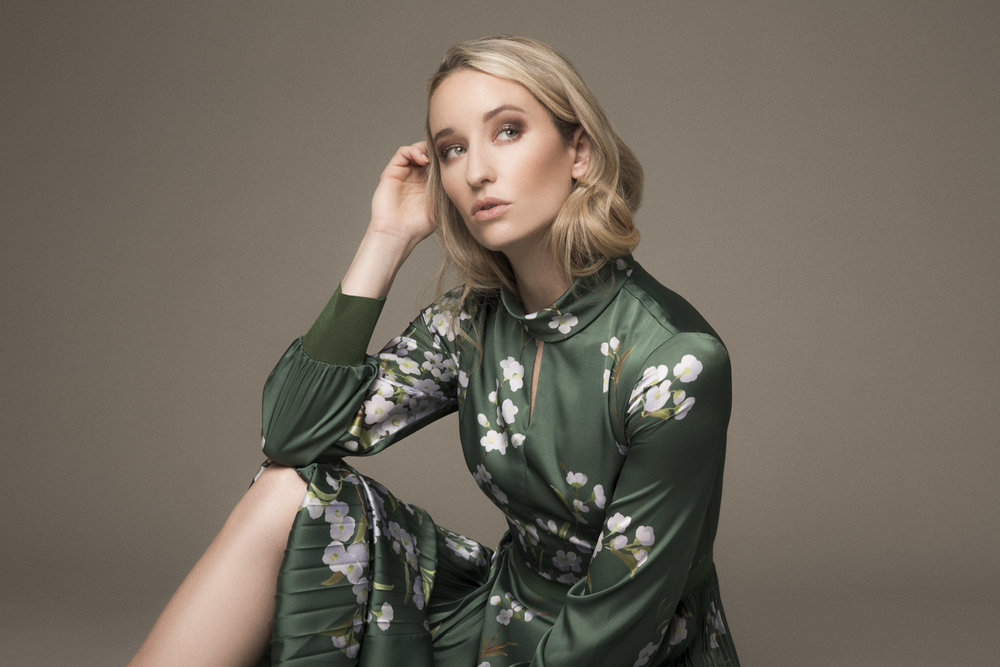 Woman sitting in a green Ted Baker dress