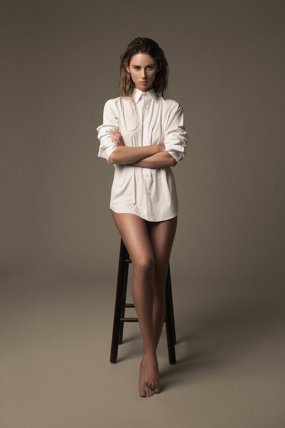 Model wearing a white dress shirt and sitting on a wood stool.
