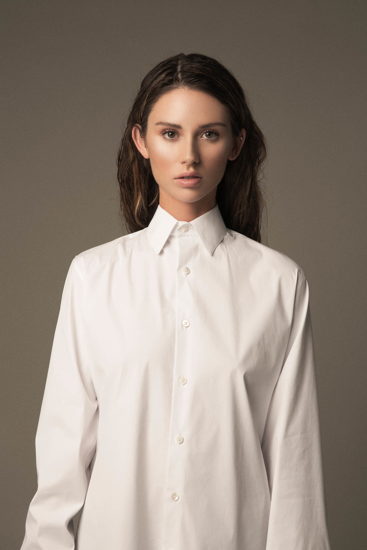 Portrait of a woman in a white men's dress shirt.