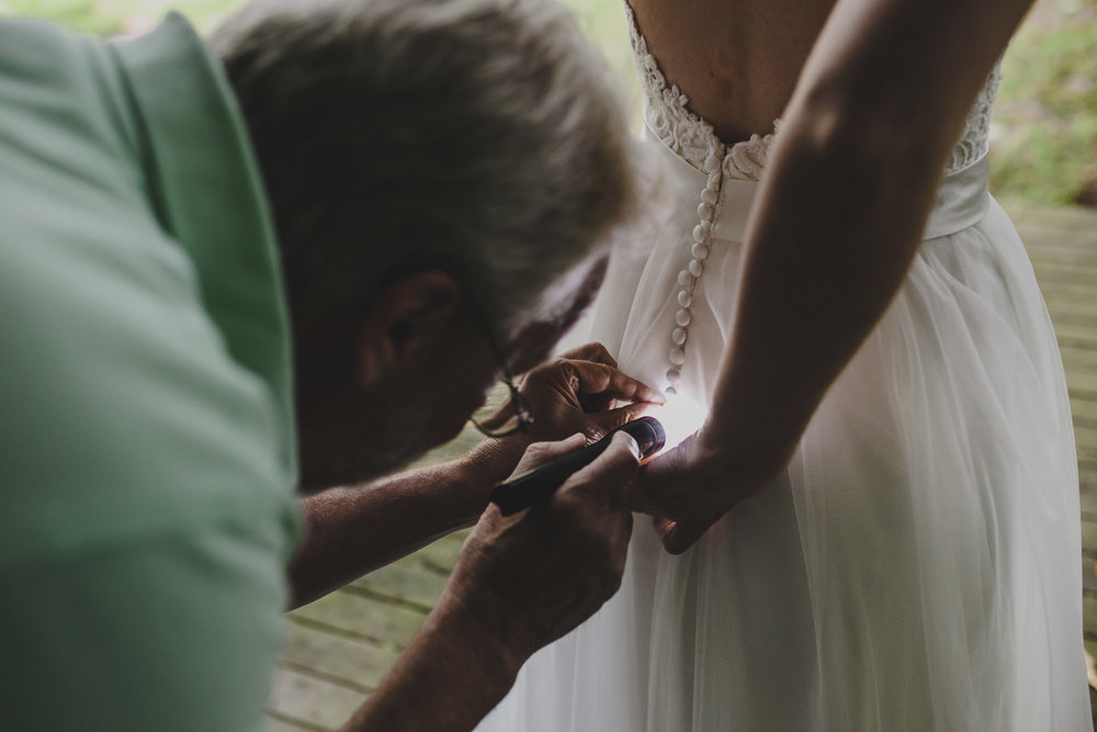 father of the bride trying to inspect the wedding dress' buttons with a flashlight