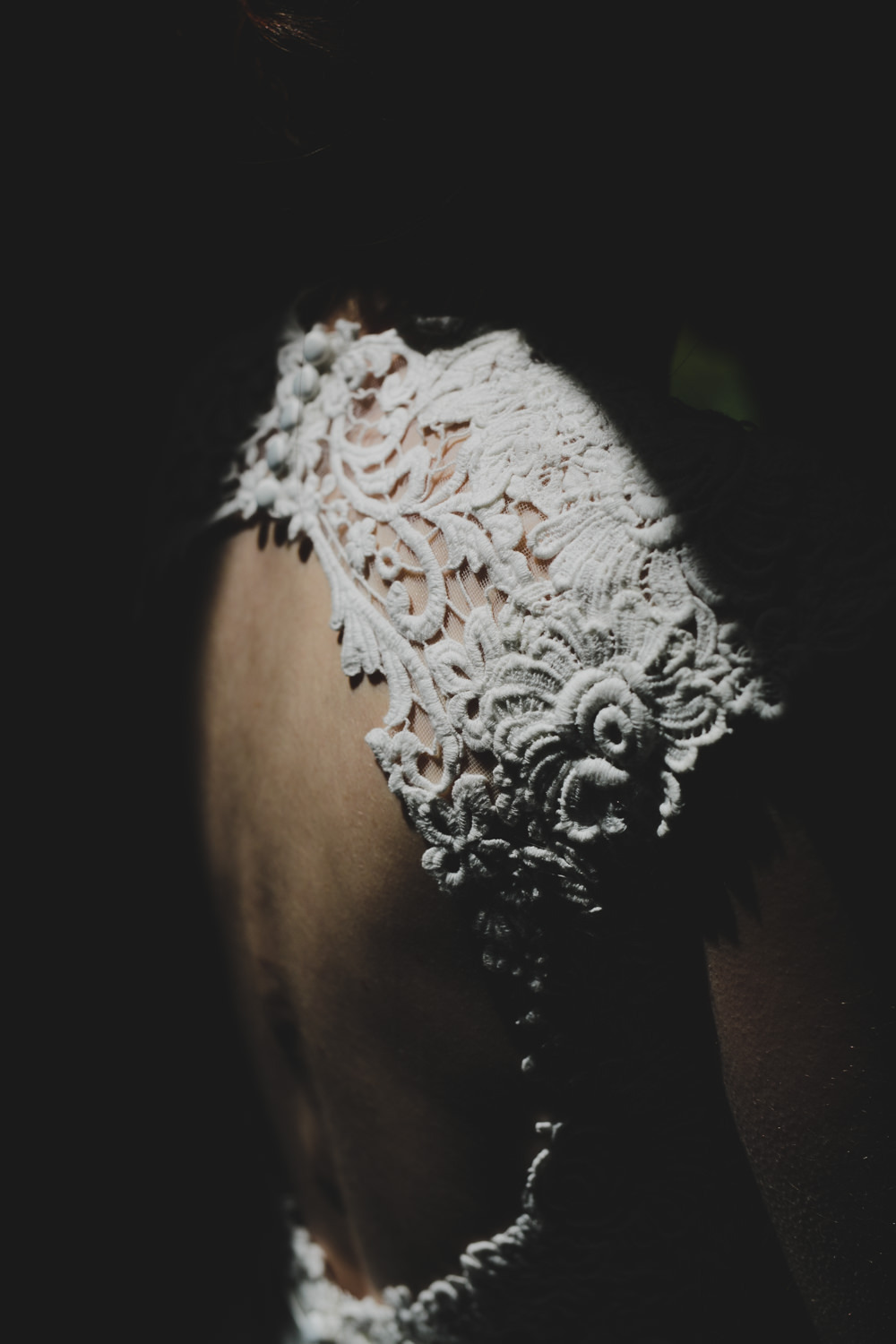 bride's detail of wedding dress in light patch