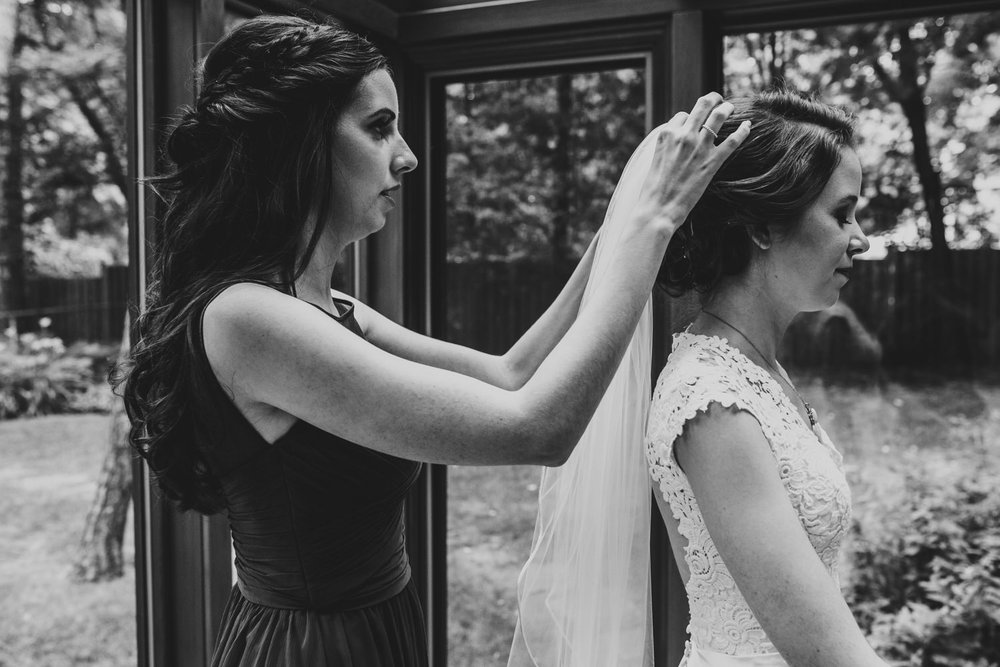 sister puts vail on bride