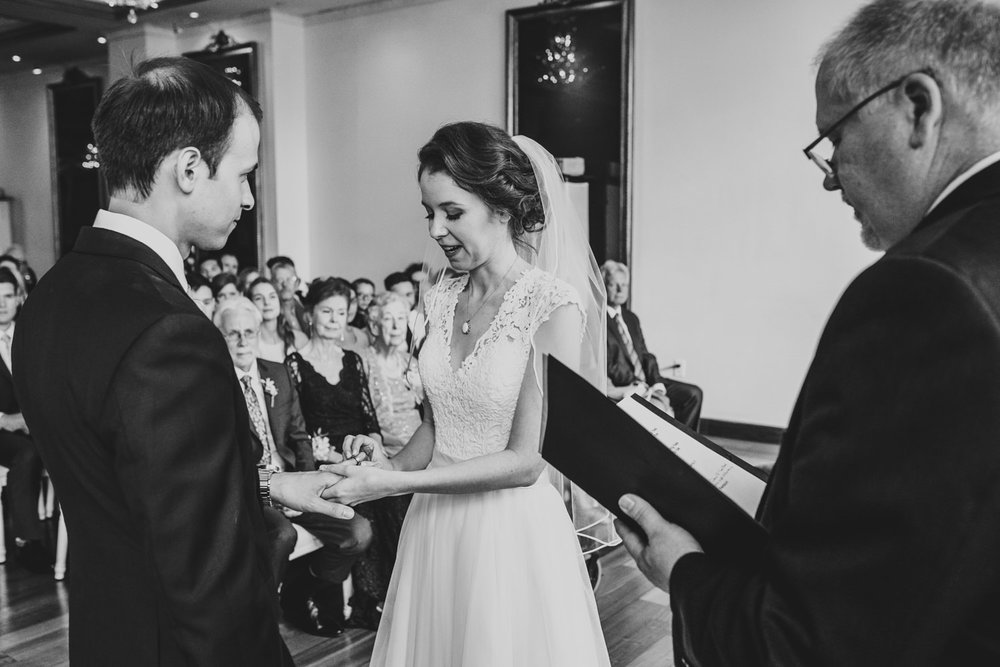 bride puts ring on groom during wedding ceremony at rosewater toronto