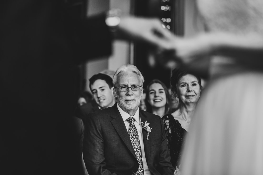 father of the bride looking at the ring exchange during wedding ceremony at rosewater toronto