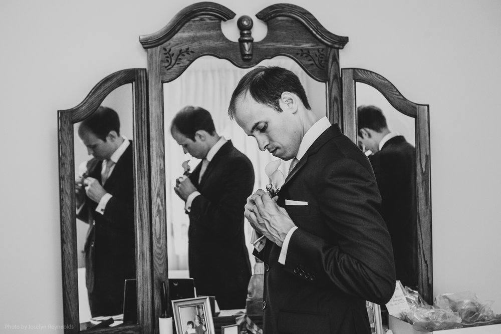 groom getting ready in mirror reflection