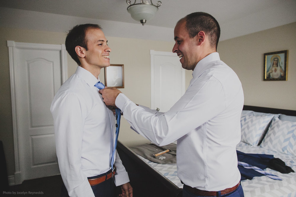 brother helps groom with tie