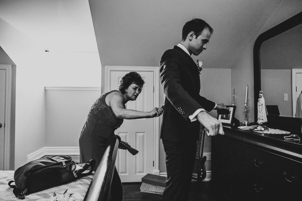 mother cleaning lint off of son's wedding suit
