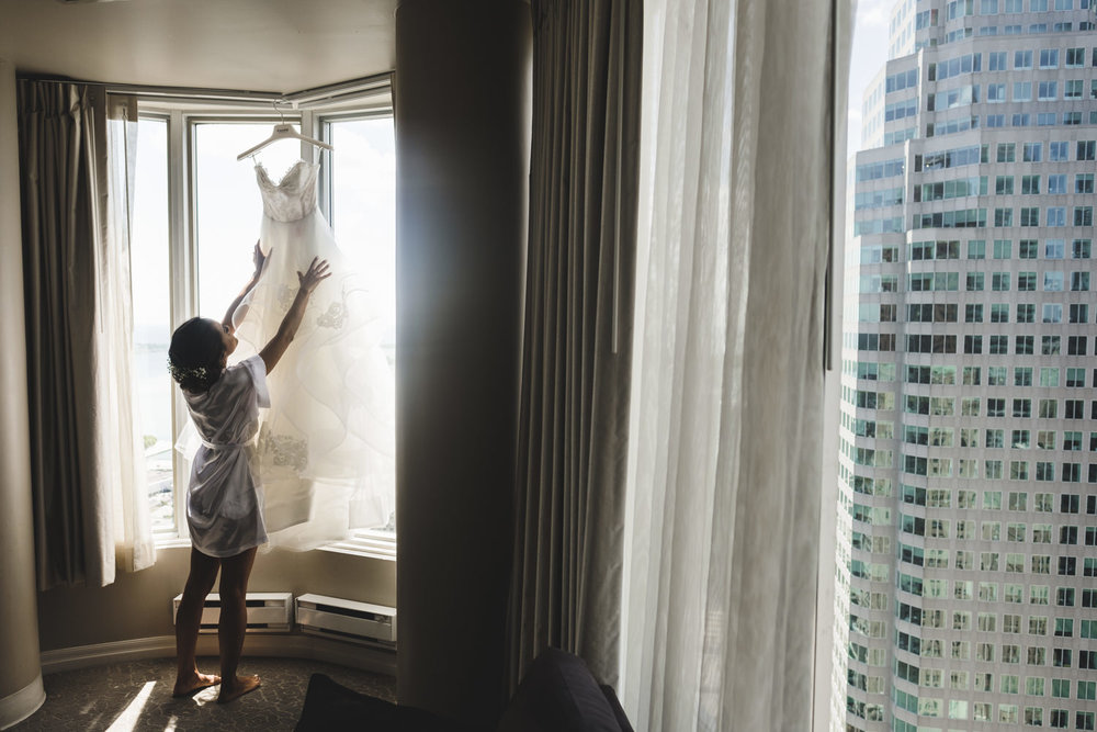 bride taking wedding dress off the window