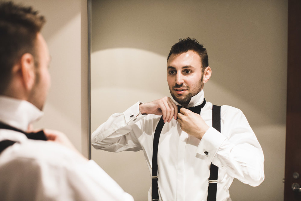 Groom adjusting bowtie
