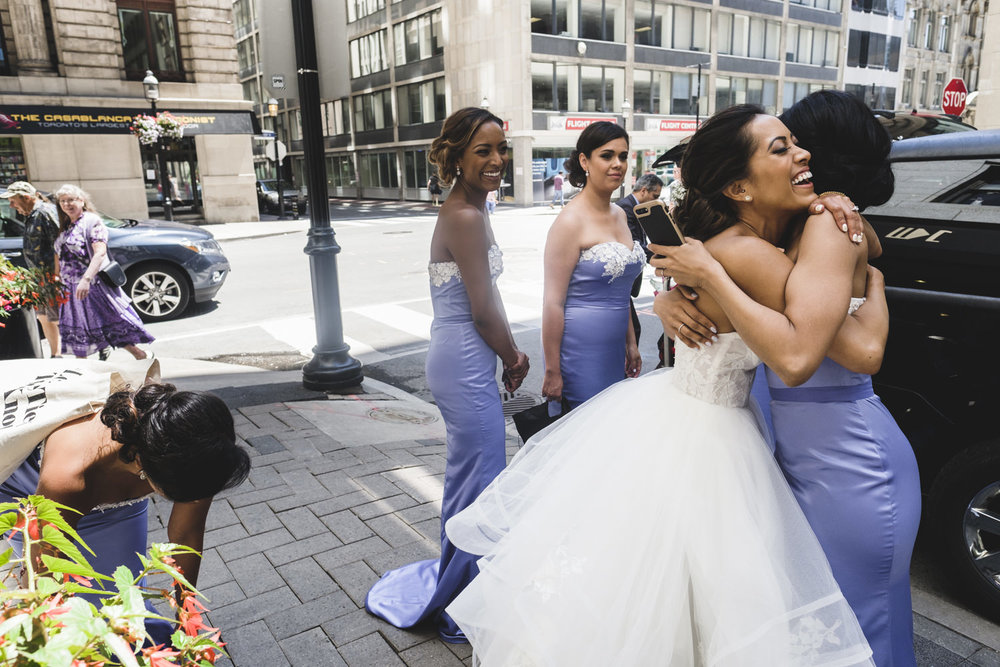 Bride hugs one of her bridesmaids before getting into the limo