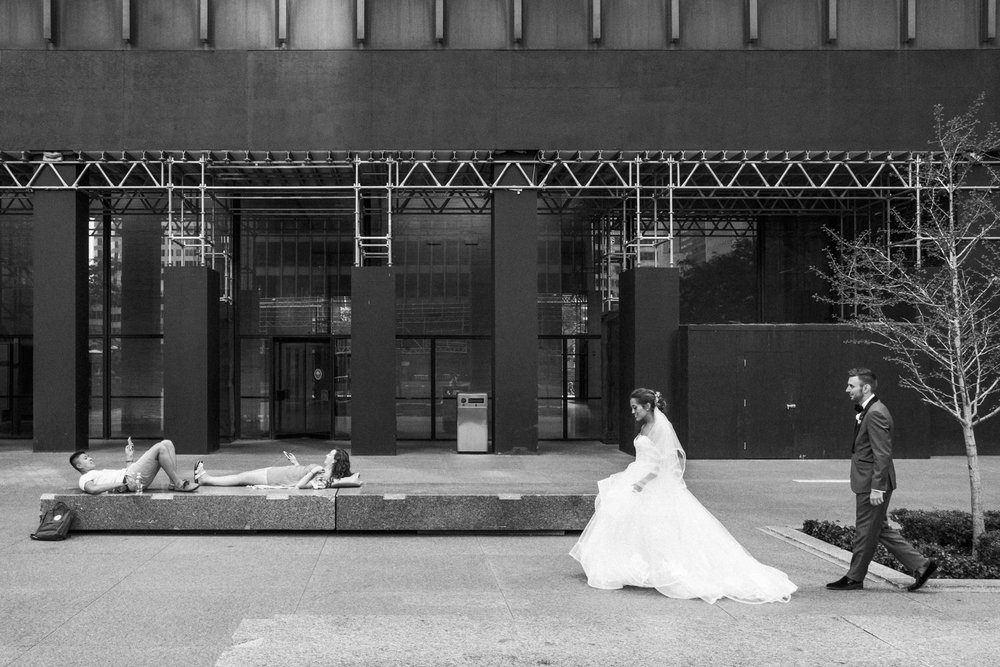 bride and groom walk by a couple relaxing and reading