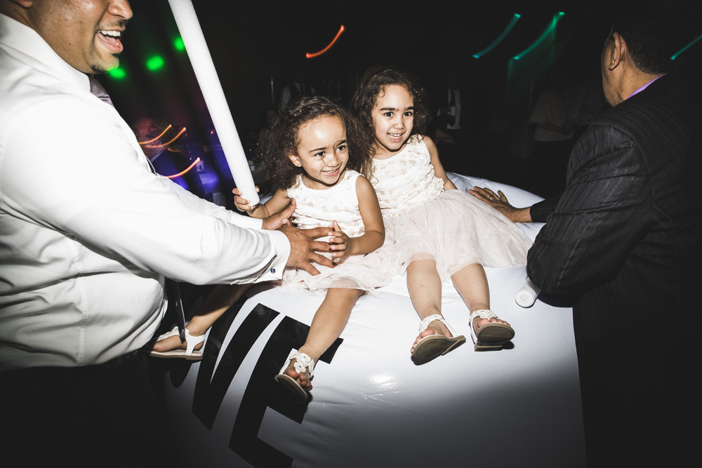 two girls sitting on love ball during wedding reception