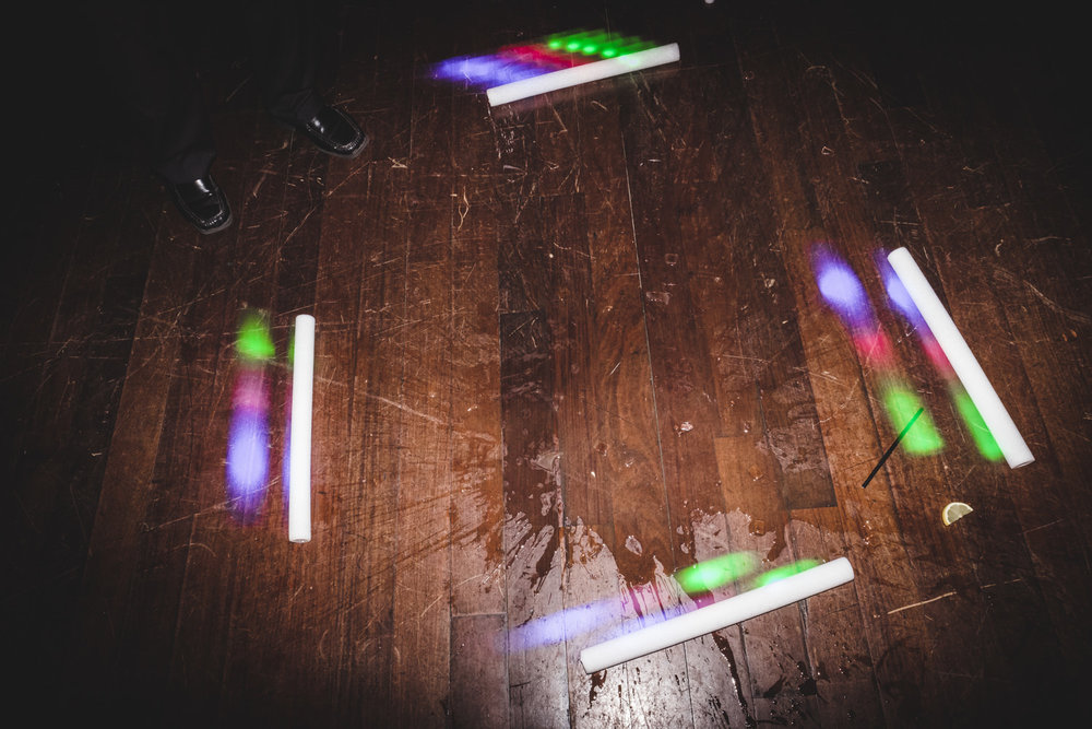 light sticks and a broken glass on the dance floor during a wedding