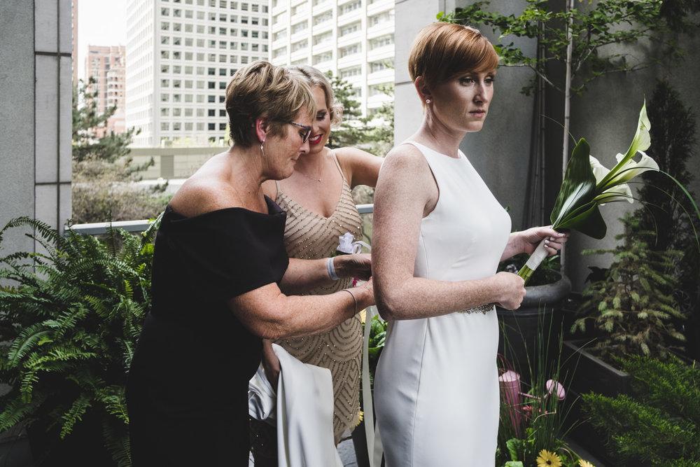 mother and sister zip up bride's wedding dress