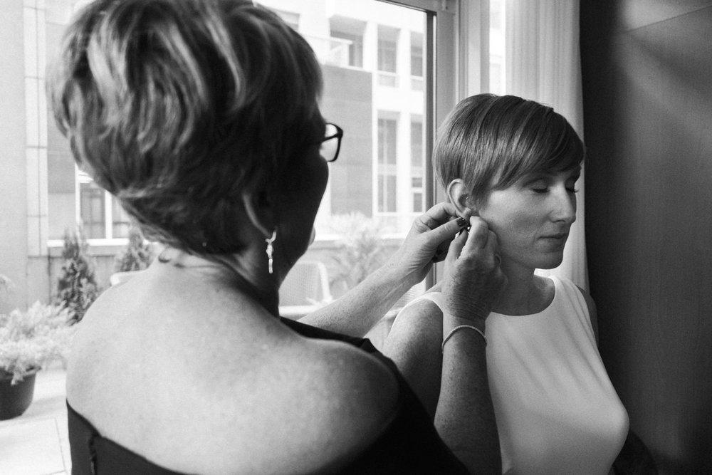 mother helps daughter put wedding earrings on