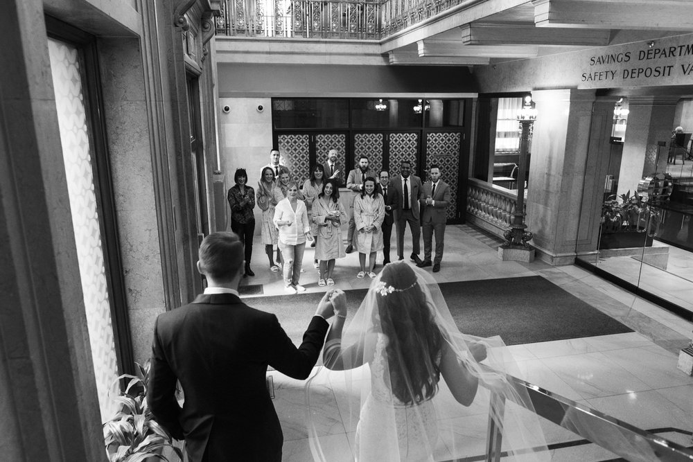 bride and groom ascend staircase after first look at one king west hotel in toronto