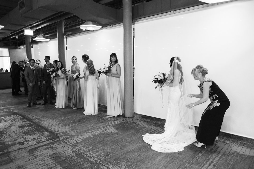 mother of bride fixing her daughter's wedding dress before walking down the aisle at 2nd floor events in toronto