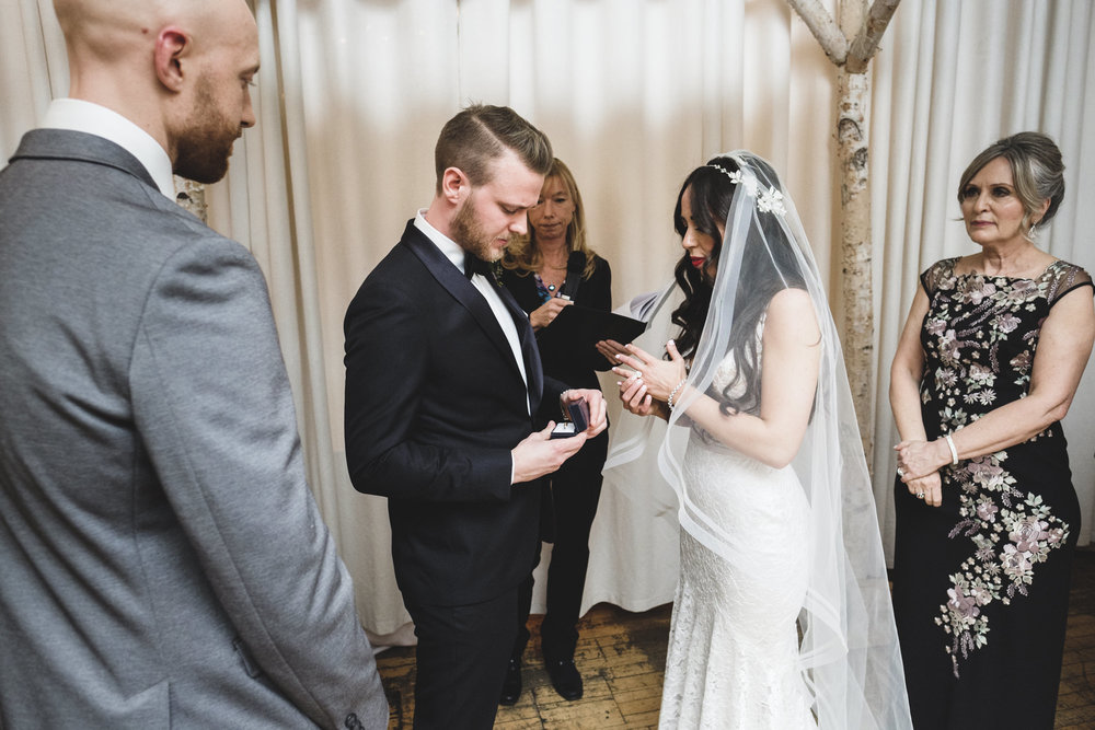 groom getting ready to put a wedding band on bride's finger during their ceremony at 2nd floor events in toronto