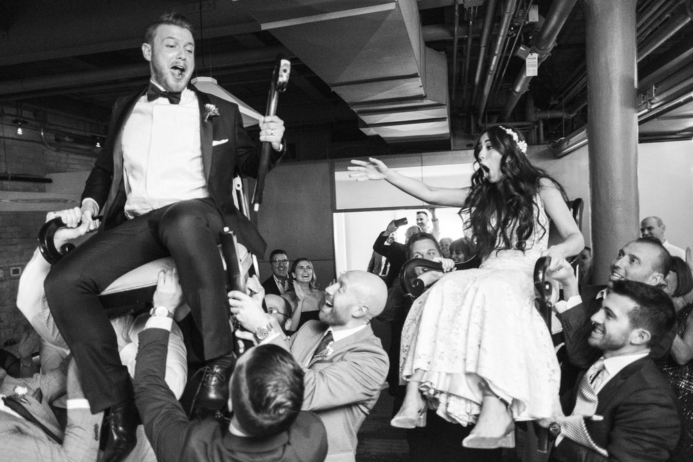 bride and groom on chairs during horah dance at 2nd floor events in toronto