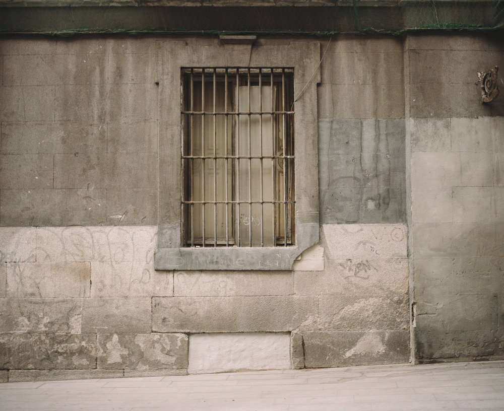 Window with bars on a grey wall, Europe