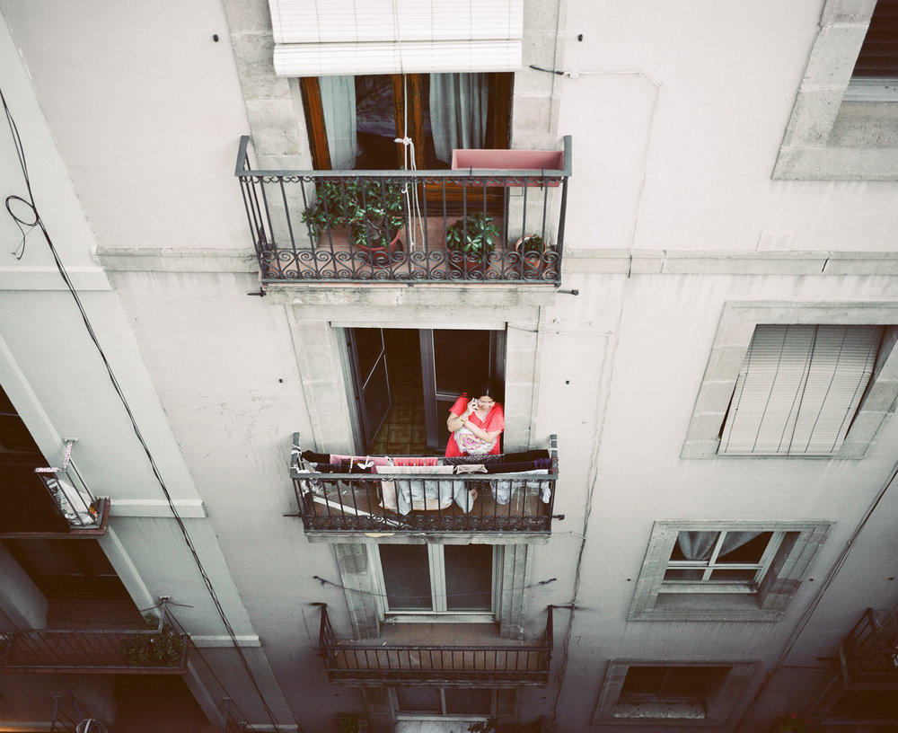 Woman on the phone standing on a balcony in Barcelona, Spain