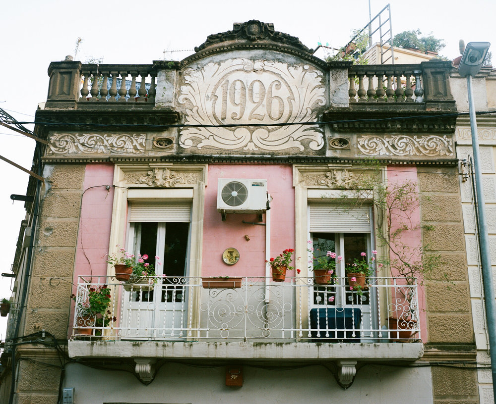 Pink house with balcony and an airconditioner, numbered 1926, in Barcelona, Spain