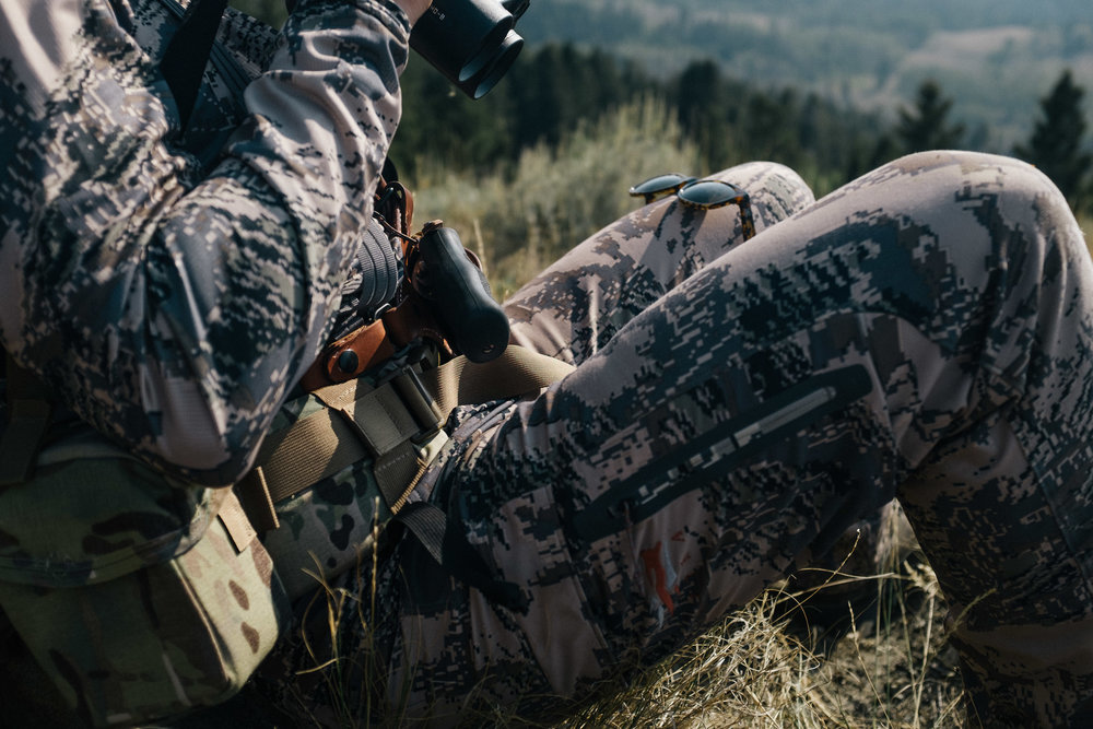 Gun in holster on hunters hip, sitka camoflage outfit