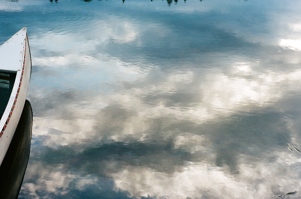 Canoe floating in a lake with cloud reflections