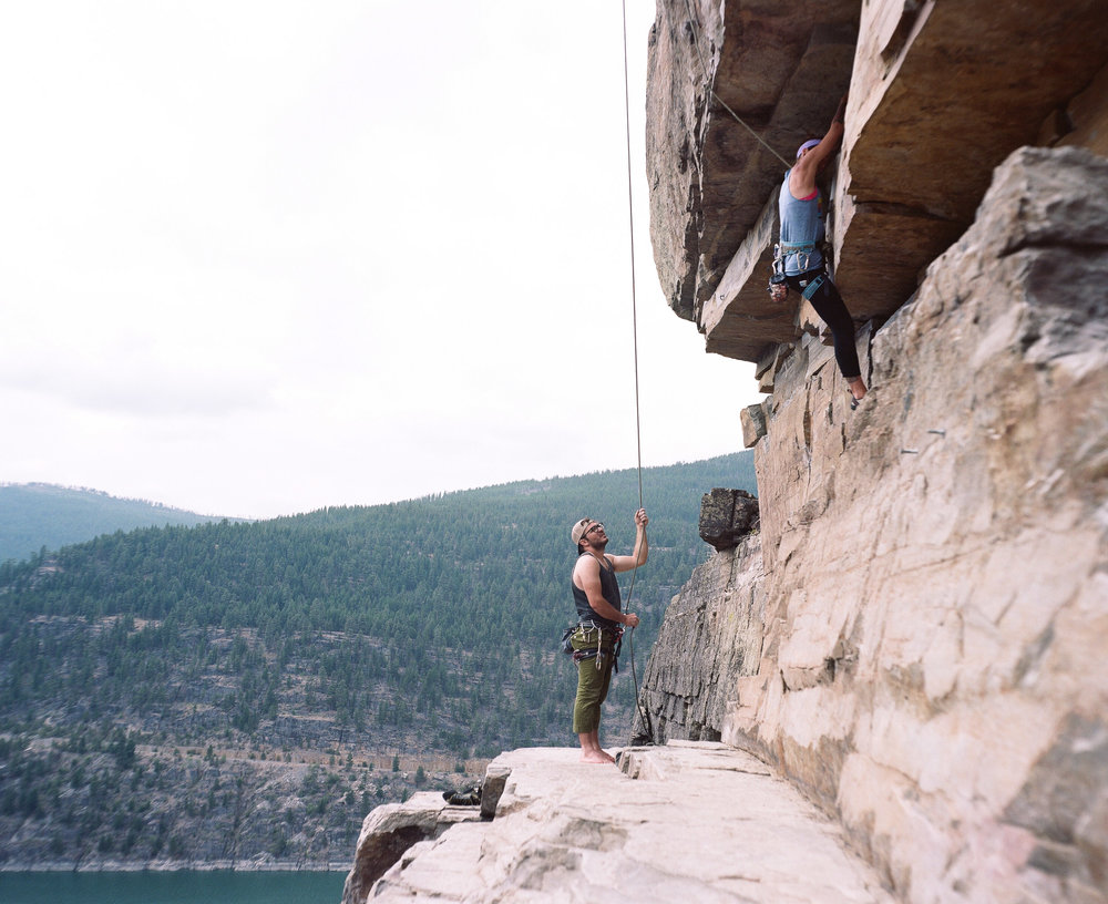 Rock climbers on a ledge over lake Koocanusa