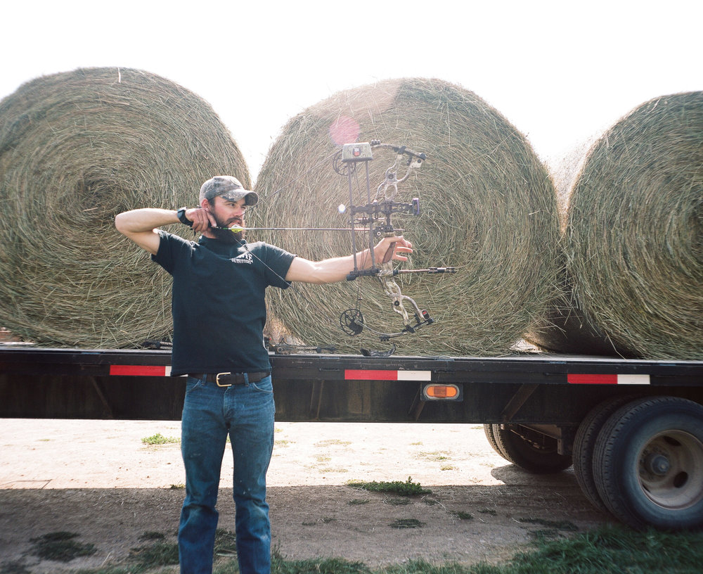 Man shooting a bow in front of bales of hay