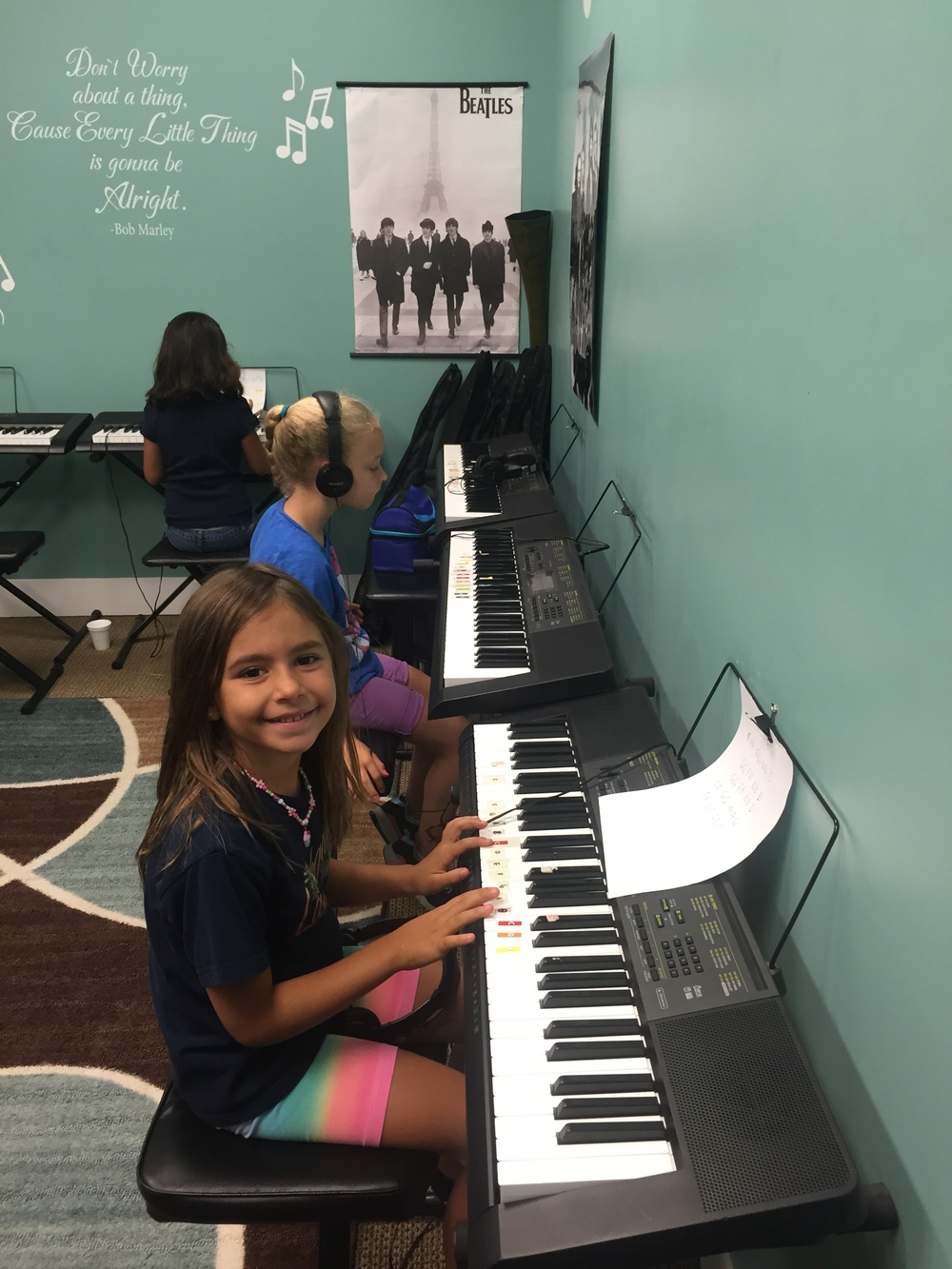 LEAH  practices her new hand position while playing her piece in group  piano class, WHILE  MADISON IS PREPARING TO PLAY A PIECE COMPLETELY MEMORIZED.